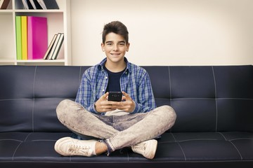 children, teenager or preteen with the mobile phone sitting on the couch