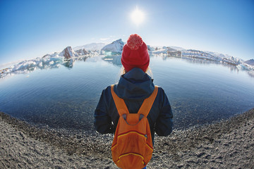 back view of girl in waterproof jacket and red knitted hat with orange backpack in Ice Lagoon in Iceland with background of sea and icebergs.