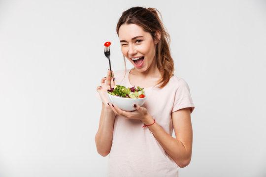 Portrait of a happy playful girl eating fresh salad