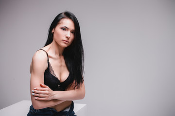 attractive sexy girl in black brassiere and jeans sitting on cube on gray studio background