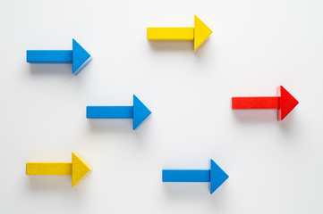 Wooden arrows on white background, one arrow in opposite direction from others. The concept of independent thinking, individuality, uniqueness. Business concept, another way.