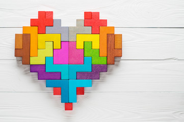 Heart made of colorful wooden shapes, top view, flat lay.