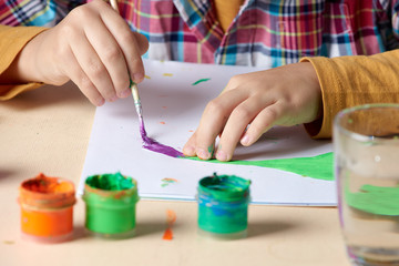 Child is painting with watercolors. Close up view.
