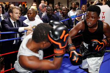 French President Emmanuel Macron looks at boxers as he visits a sport center in the Jamestown area in Accra