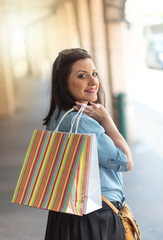Young woman walking with shopping bags in hand