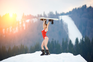 Young female snowboarder wearing red bodice, smiling, holding her snowboard above a head, standing on snowy hill at ski resort. Ski season and winter sports concept