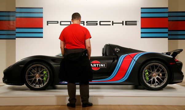"A guest looks at a 2015 Porsche 918 ""Weissach"" Spyder is displayed during a media preview for the ""RM Sotheby's Icons"" sale at Sotheby's in New York"