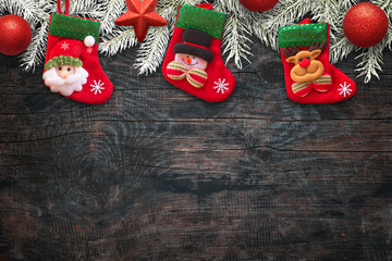 Kids sock on wooden table waiting for Santa Claus gifts. Free space for text bottom on wooden board. Top view.