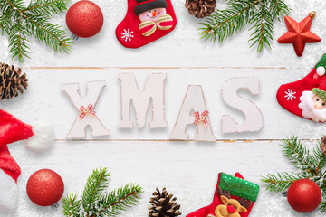 Xmas decorated text on white wooden board surrounded with decorations, socks, hat, fir branches and pinecones.