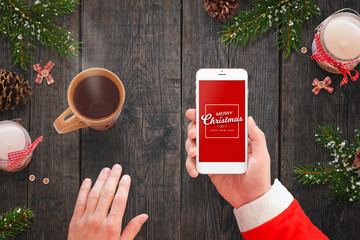 Santa holding smart phone with Merry Christmas message on screen and drink hot tea. Candles and fir branches beside.