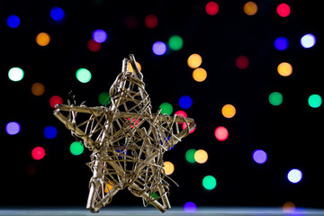 A celebratory Christmas star on a wooden table. Christmas decorations on the background of Christmas lights.