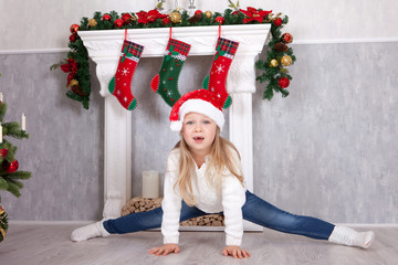 Gymnastic pose, stretch. Little blonde girl in the Santa hat, doing cross-twine exercising. Doing a full split in Christmas interior