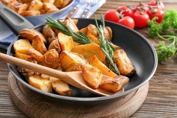 Pan with delicious rosemary potatoes on wooden table
