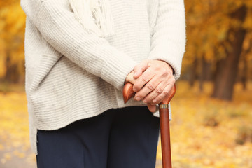 Senior woman with cane in park, closeup