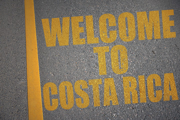 asphalt road with text welcome to costa rica near yellow line.