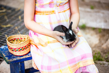 Girl holds a bunny in a basket