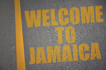 asphalt road with text welcome to jamaica near yellow line.