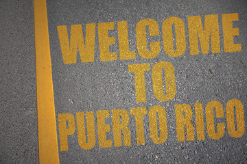 asphalt road with text welcome to puerto rico near yellow line.