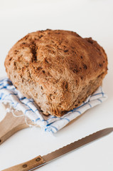 Loaf of rustic farmers market wholegrain rye bread with fried onion baked in a woode fired oven on kitchen towel and wooden cutting board with bread knife on white background