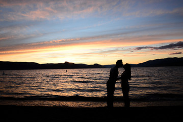 Couple kissing on sunset in front of the lake