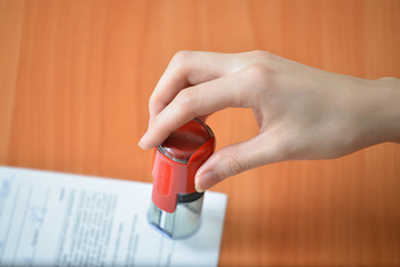 Female hand hold rubber stamps over documents and papers at office table, closeup detail shoot.