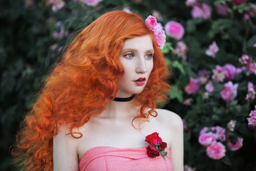 Red-haired girl with curly hair with pale skin in a summer dress with a rose in her hair in the garden.