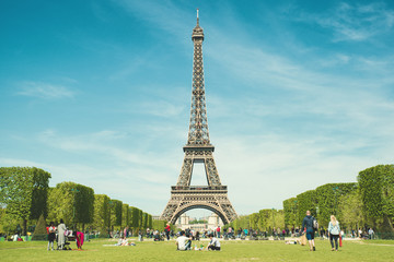 Paris, France - May 6,2016 : Tourists chilling in park near Eiffel Tower Paris, France. In year 2016 more than 15 million tourists visited the city of Paris.