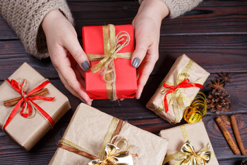 Woman hands with gift box, decorated with golden ribbon, on dark wooden table, top view. Holiday presents, Christmas time concept