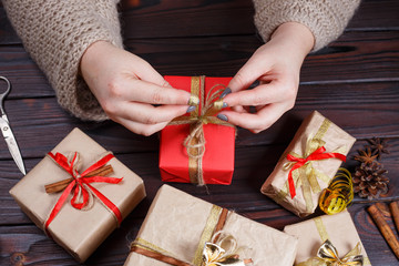 Woman hands making bow at Christmas gift box, decorated with golden ribbon, on dark wooden table, top view. Holiday presents, Christmas time concept