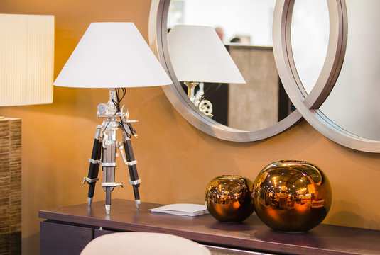 Modern room design. ?hest of drawers with a table lamp on a tripod, copper round decorative vases