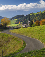 curved road and view to Italian village in Alpines