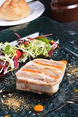 Duck terrine with salad on dark slate