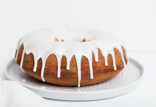 Homemade lemon bundt cake with thick lemon icing on light grey plate with coth napkin and cake forks on white wooden table