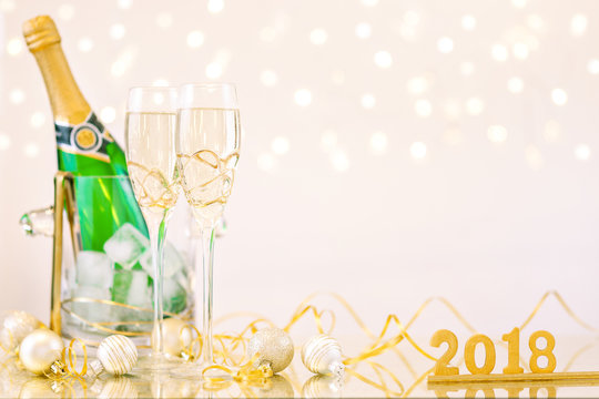 New Year Celebration with Champagne Glasses and a Bottle 2018. New Year flutes with bubbling champagne and a bottle on the beige background with bokeh.
