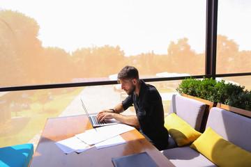 Freelance copywriter rewrite text on laptop at cafe table.