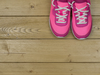 A pair of pink women's shoes on the floor of wooden planks.