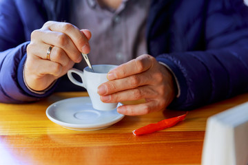 man with cup of coffee. Young male person in casual clothes having hot drink in cafe