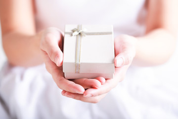 Close up of female hands holding a small gift wrapped with ribbon. Christmas concept