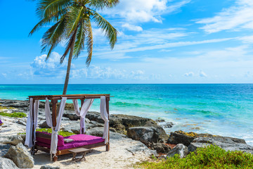 Beach beds under the palm trees on paradise beach at tropical Resort. Riviera Maya - Caribbean coast at Tulum in Quintana Roo, Mexico