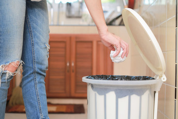Woman putting empty plastic bag in recycling bin in the kitchen.
