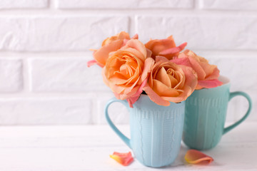 Fresh orange roses in blue cups