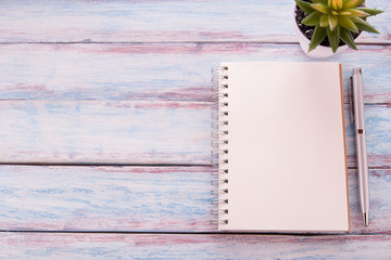 Flat lay photo with blank notebook, pen and cuctus flower on wooden table background.