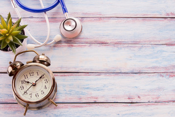 Flat lay photo with vintage alarm clock and blue stethoscope on wooden table background.