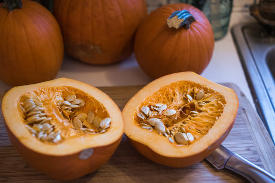 Sugar pumpkin cut in half exposing the pulp and seeds