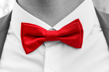 Red bow tie on neck of man, black and white photo with coloured element