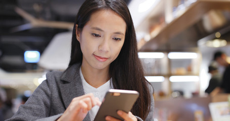 Asian Business woman use of smart phone in restaurant