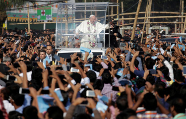 Pope Francis greets believers as he arrives for a mass in Dhaka