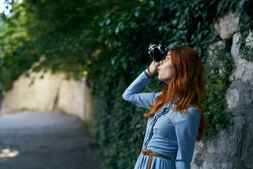 Young beautiful woman in a blue dress makes a photo on her camera in an alley on the street