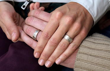 Gay married couple David Mullins and Charlie Craig show their wedding rings for a photo in Denver