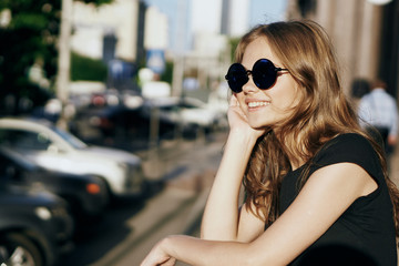 Young beautiful woman in round sunglasses on the street in the city